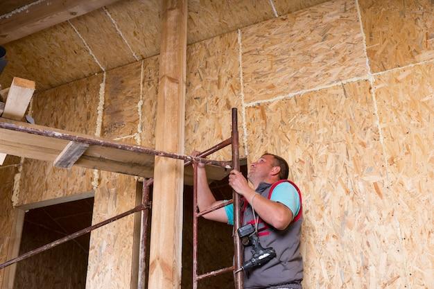 무선 드릴을 들고 남성 건설 노동자 빌더 노출된 입자 합판 보드 프레임 미완성된 집 내부 비계의 사다리를 등반