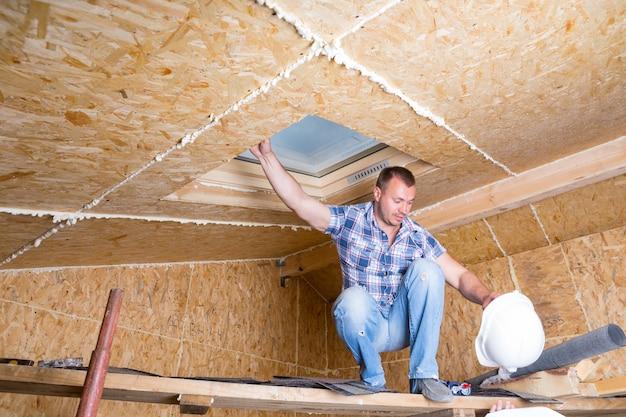 흰색 안전모를 들고 노출된 파티클 합판 보드가 있는 미완성된 집의 천장 근처에 있는 나무 판자 비계에 남성 건설 노동자 빌더