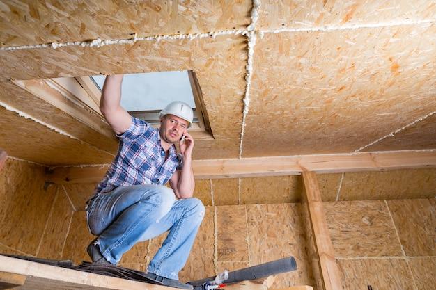 露出した粒子合板のある未完成の家の中の天窓で天井近くの高架足場にしゃがみ込んでいる携帯電話の男性建設労働者ビルダー