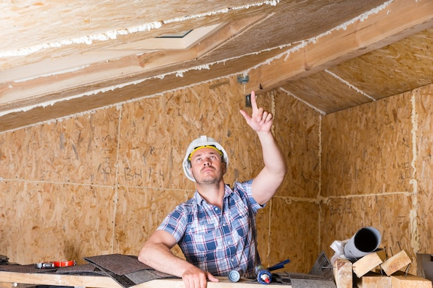 남성 건설 노동자 빌더가 천장을 가리키고 올려다보고, 수공예품에 감탄하고, 노출된 입자 합판 보드가 있는 미완성 집 내부