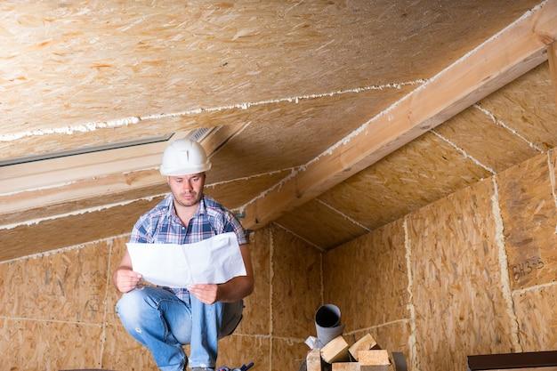 노출된 합판 파티클 보드가 있는 미완성 집 천장 근처의 높은 비계 및 독서 계획에 웅크리고 있는 흰색 안전모를 쓴 남성 건설 노동자 빌더