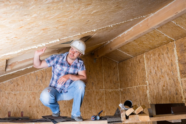 노출된 파티클 합판 보드가 있는 미완성된 집의 천장 근처 높은 비계에 웅크리고 있는 흰색 안전모를 쓴 남성 건설 노동자 빌더