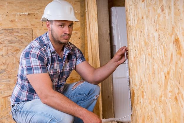 노출된 입자 합판 보드가 있는 미완성된 집 내부의 줄자로 도어 프레임을 측정하는 흰색 하드 모자를 쓴 남성 건설 노동자 빌더