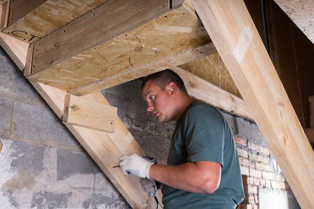 노출된 시멘트 벽이 있는 미완성 집 지하실의 계단용 무선 드릴 빌딩 프레임이 있는 남성 건설 노동자 빌더