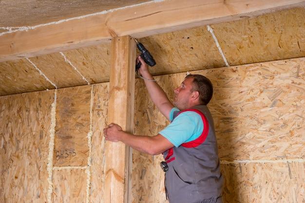 노출된 합판 파티클 보드가 있는 미완성된 집에 나무 프레임에 무선 드릴 드릴링 나사가 있는 남성 건설 노동자 빌더