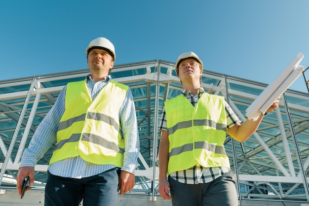 Male construction worker and engineer at the construction site.