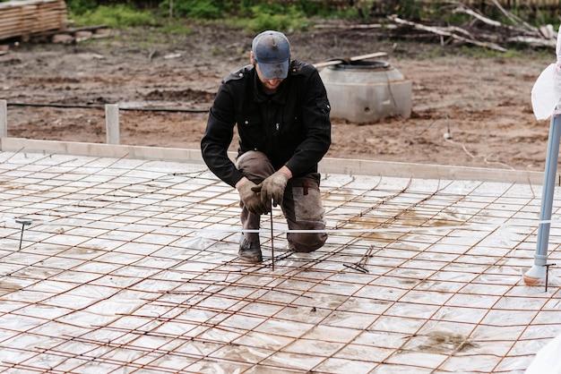 男性の建設労働者は、コンクリートを注ぐための家の建設の基礎のために鉄筋を準備します