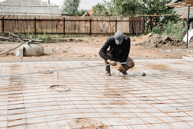 Male construction worker prepares rebar for foundation of construction of house and pouring concrete
