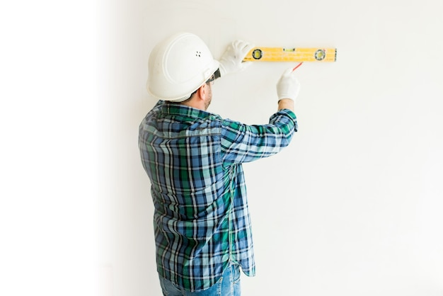 Male construction worker in protective helmet applies level to white smooth wall in construction area