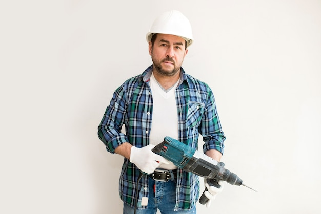 Male construction worker in a protective helmet with a perforator on a white