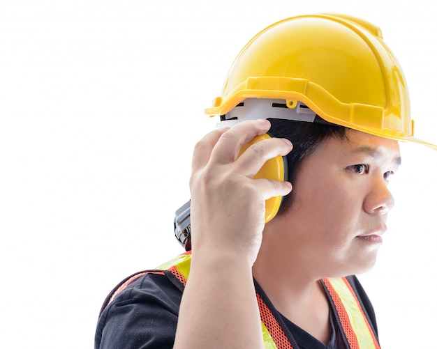 Male construction worker with standard construction safety equipment and closeup at ear muffs isolated
