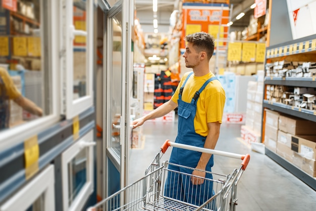 Мужской конструктор, выбирая окна в строительном магазине. строитель в униформе осматривает товары в магазине своими руками
