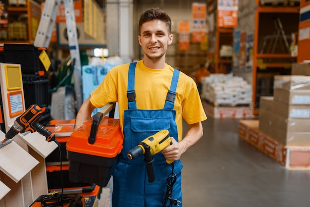 Male constructor holds tools in hardware store. builder in uniform look at the goods in diy shop