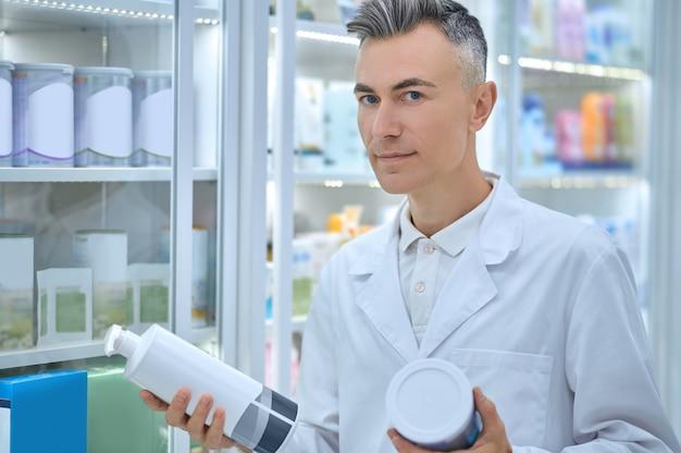 Фармацевт-консультант мужского пола, держа в руках продукты здравоохранения