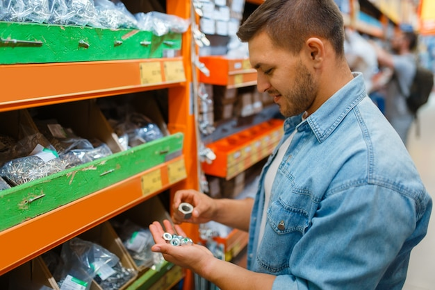 Male consumer choosing nuts in hardware store.