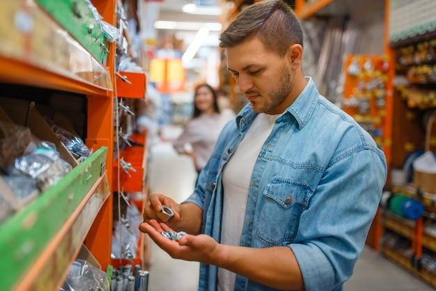 Потребитель мужского пола, выбирающий орехи в строительном магазине.