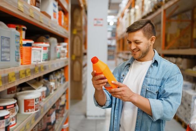 Male consumer choosing repair materials in hardware store. customer look at the goods in diy shop