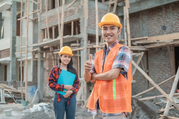 Male contractor stands with crossed hands smiling at the camera wearing a safety helmet against a female construction worker in the background