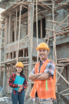 The male contractor stands with his crossed hands smiling at the camera wearing a safety helmet and vest