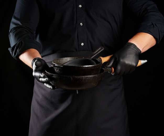 Male cook in black uniform and latex gloves holds an empty round vintage black cast iron pan