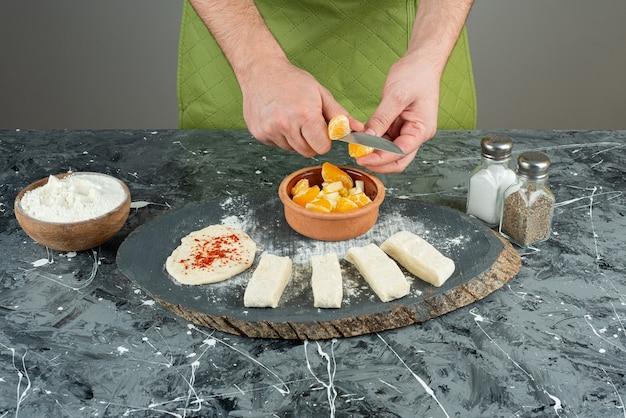 男性の料理人は、大理石のテーブルの上でオレンジを細かく切ります。