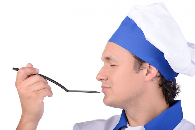 Male cook delightfully smelling the contents of spoon.