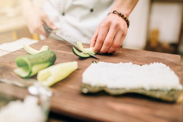 Мужской повар руки крупным планом, делая суши-роллы на кухне.
