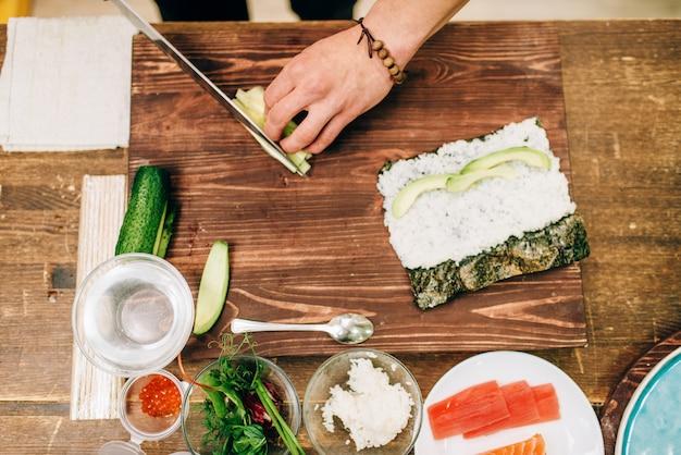 Мужские руки повара делают суши-роллы