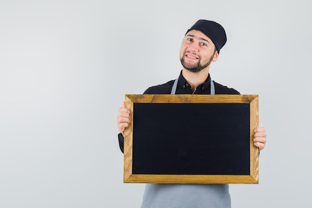 Male cook holding blackboard in shirt, apron and looking merry. front view.