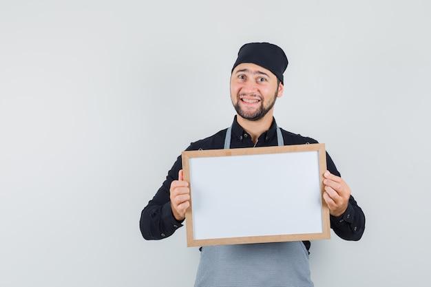 シャツ、エプロンでホワイトボードを保持し、陽気に見える男性料理人、正面図。