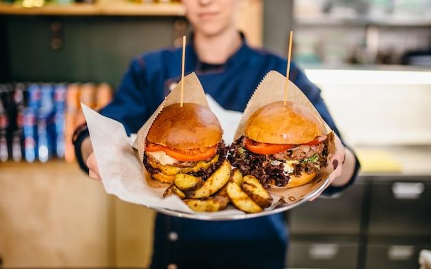 Мужской повар держит в руках жареный картофель и свежие гамбургеры.