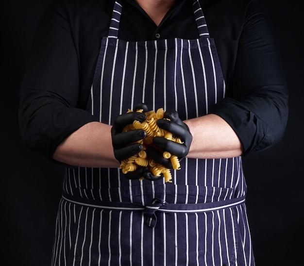 縞模様のエプロンを着た男性料理人と黒いラテックス手袋は生のフーを握ります