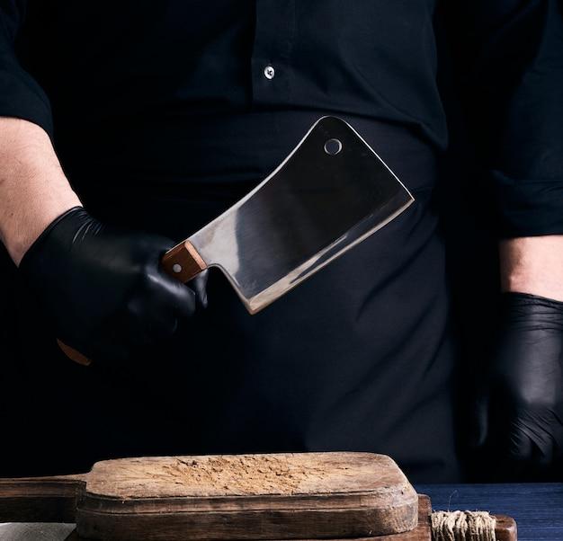 黒のユニフォームと黒のラテックス手袋の男性料理人がまな板の上に大きな鋭い肉ナイフを持っています