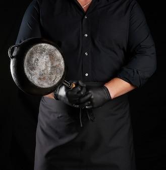 Мужчина-повар в черной униформе и латексных перчатках держит перед собой пустую круглую винтажную черную чугунную сковороду, сдержанно