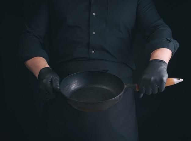 黒のユニフォームとラテックスの手袋をはめた男性料理人が空の丸いヴィンテージ黒鋳鉄鍋を保持しています。