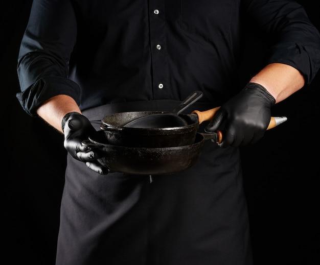 Мужчина-повар в черной форме и латексных перчатках держит пустую круглую винтажную черную чугунную сковороду