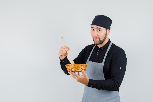 シャツを着た男性料理人、木のスプーンで食べ物を混ぜてキュートに見えるエプロン、正面図。