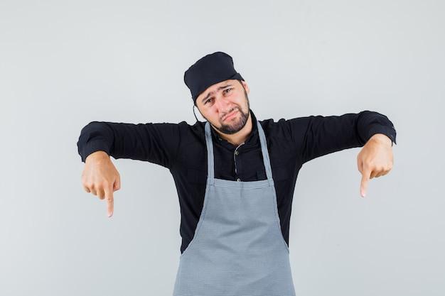 シャツを着た男性料理人、下を向いて必死に見えるエプロン、正面図。