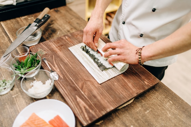 男性料理人がシーフード、アジアのキッチンを作る