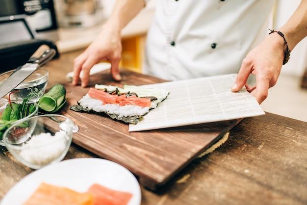 男性のコックが木製のテーブル、アジアのキッチンの準備プロセスで寿司を作ります。