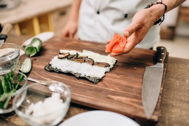 男性料理人が木製のテーブルで寿司を作る