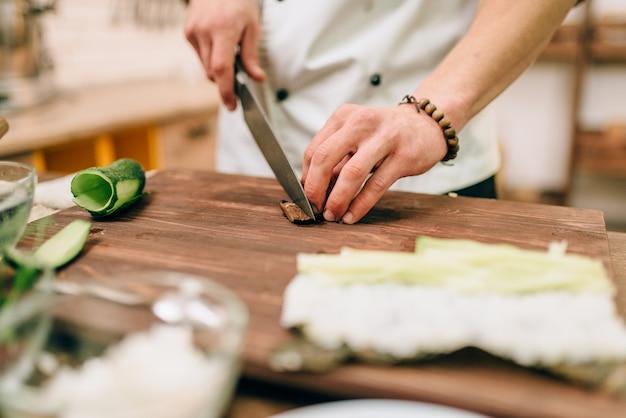 Мужской повар, делающий суши-роллы на деревянном столе