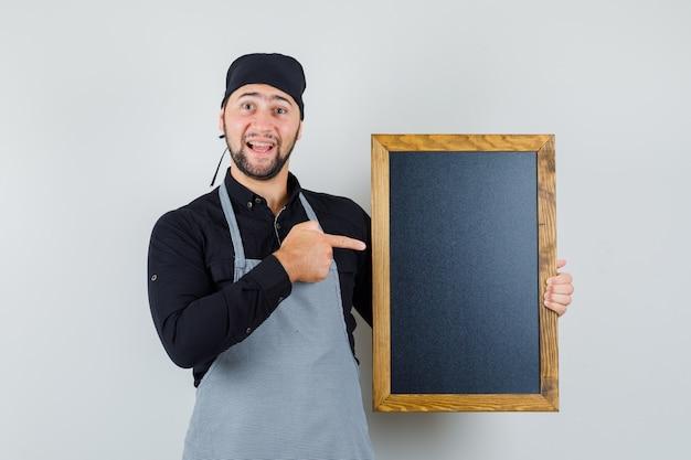셔츠, 앞치마에 칠판을 가리키고 행복을 찾는 남성 요리사. 전면보기.