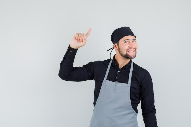 男性の料理人はシャツ、エプロンで上向きで陽気に見えます。正面図。