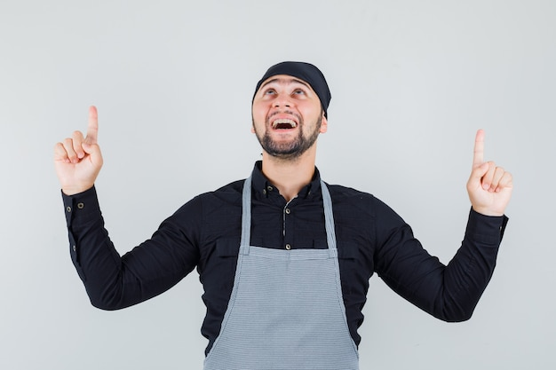 男性の料理人はシャツ、エプロンで上向きになり、感謝しているように見えます。正面図。