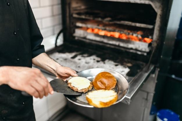 Мужской повар готовит вкусное мясо на гриле, приготовление бургеров.