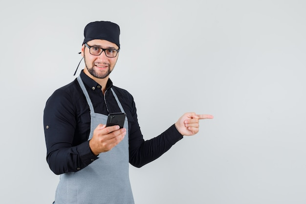 Cuoco maschio in camicia, grembiule che tiene il telefono cellulare mentre indica lontano e sembra allegro, vista frontale.