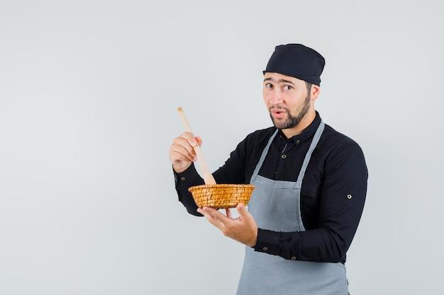 Cuoco maschio in camicia, grembiule che mescola il cibo con un cucchiaio di legno e sembra carino, vista frontale.