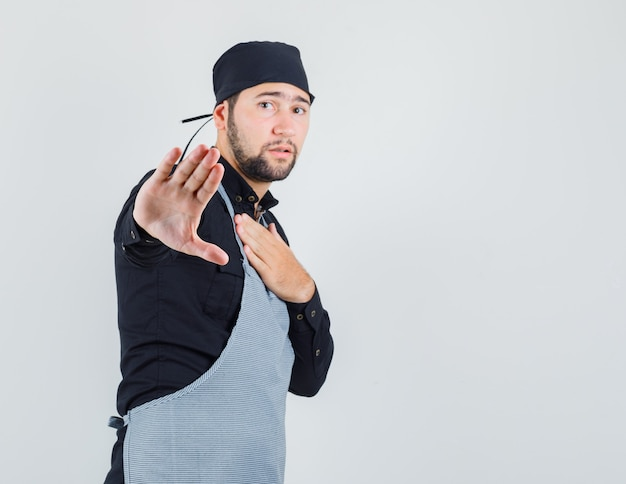 Male cook in shirt, apron showing refusal gesture and looking exhausted , front view.