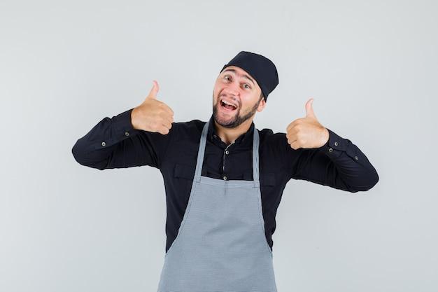 男性の料理人はシャツ、エプロンで二重の親指を示し、幸運に見えます。正面図。